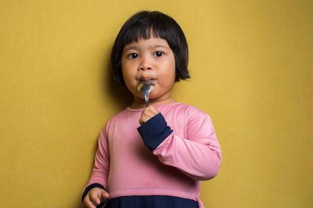 Menina asiática faminta segurando uma colher na parede amarela