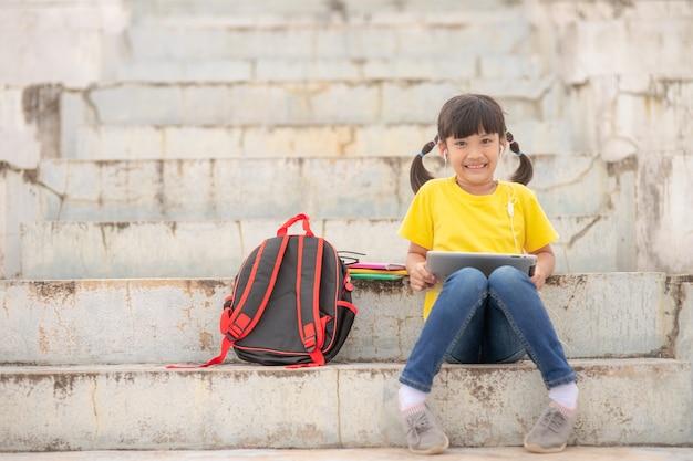 Menina asiática fazendo aula on-line e feliz