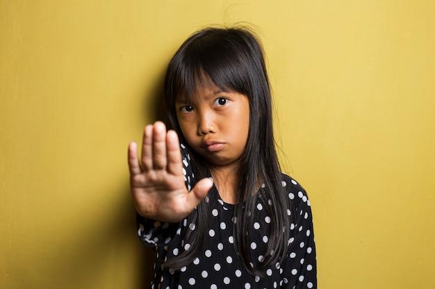 Menina asiática fazendo gesto de parada com a mão