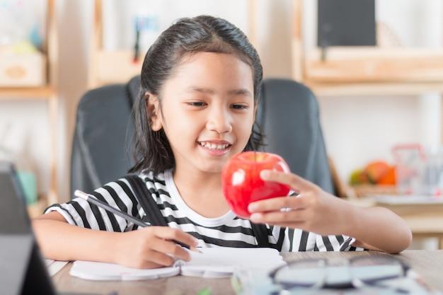Menina asiática fazendo lição de casa