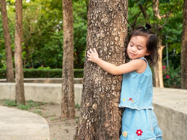 Menina asiática feliz 3-4 anos de idade abraçando o tronco da árvore no parque.