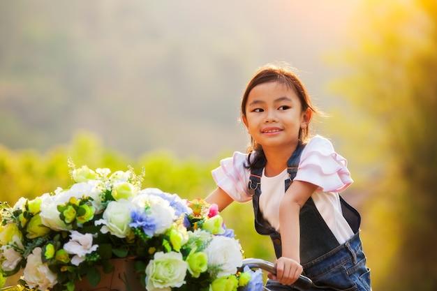 Menina asiática feliz andando de bicicleta com flores na cesta