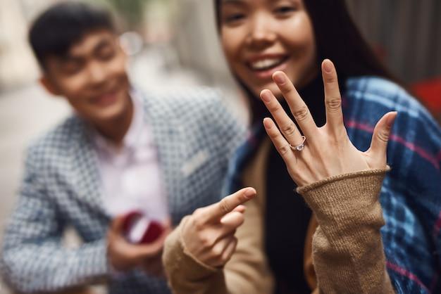 Menina asiática feliz apontando para tocar no dedo.
