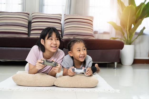 Menina asiática feliz com a irmã jogando videogame usando joystick ou controlador enquanto estava deitada no chão em casa