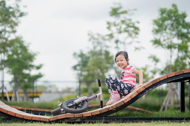 Menina asiática feliz criança andar de bicicleta no parque infantil
