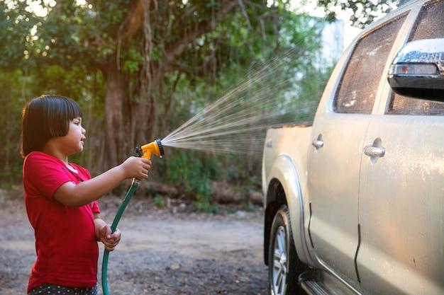 Menina asiática feliz da criança da ajuda do pai que lava o carro na água que espirra com a luz solar