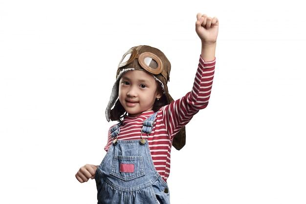 Menina asiática feliz da criança pequena no traje do piloto com expressão da paixão