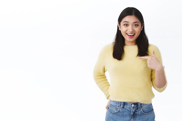 Menina asiática feliz e animada apontando para a surpresa de si mesma ao ouvir boas notícias, ganhando um prêmio incrível, sorrindo otimista, sentindo-se feliz e satisfeita por ter alcançado o sucesso, parede branca de pé