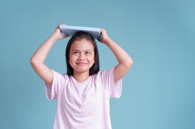 Menina asiática feliz em pé colocando o livro na cabeça