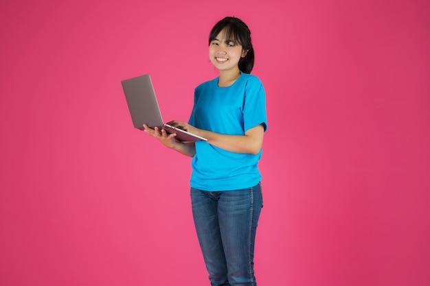 Menina asiática feliz em pé usando laptop em fundo rosa