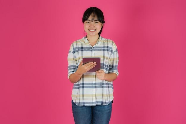 Menina asiática feliz em pé usando tablet em fundo rosa