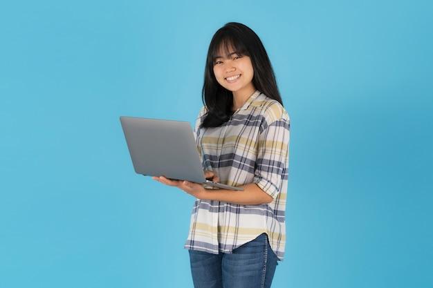 Menina asiática feliz em pé, usando um laptop em um fundo azul