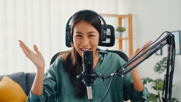 Menina asiática feliz grava um podcast com fones de ouvido e microfone falando e descansa no quarto dela