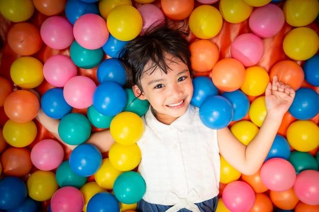 Menina asiática feliz jogando na piscina de bolas coloridas