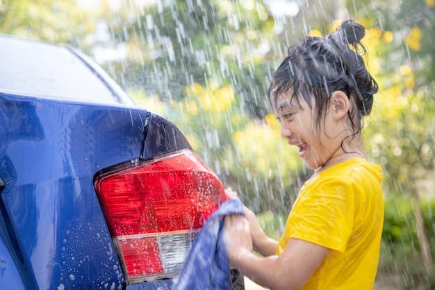 Menina asiática feliz lavando carro com respingos de água e luz do sol em casa