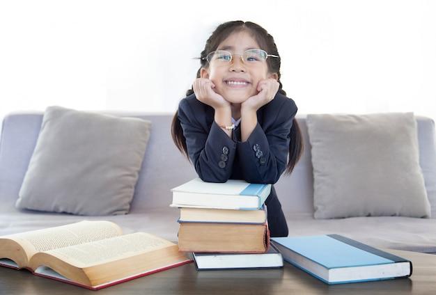 Menina asiática feliz lendo livro na sala de estar