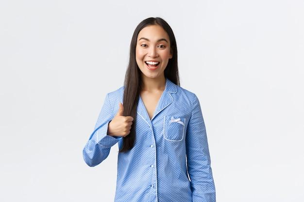 Menina asiática feliz otimista de pijama azul sorrindo satisfeita e mostrando o polegar para cima em aprovação ou tipo, recomendar produto, ótima qualidade, mostrando bem feito ou bom trabalho, fundo branco.