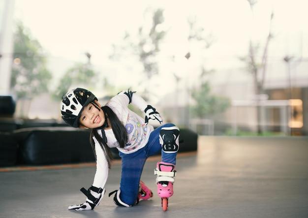 Menina asiática feliz que aprende ao patim de rolo. crianças usando almofadas de proteção para passeio seguro.