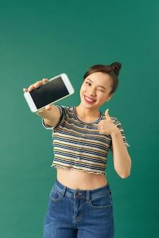 Menina asiática feliz satisfeita mostrando o polegar para cima ao demonstrar o aplicativo da tela do celular, fundo verde em pé, recomendar o aplicativo