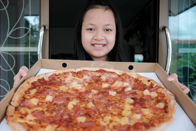 Menina asiática feliz segurando uma grande entrega de pizza em casa
