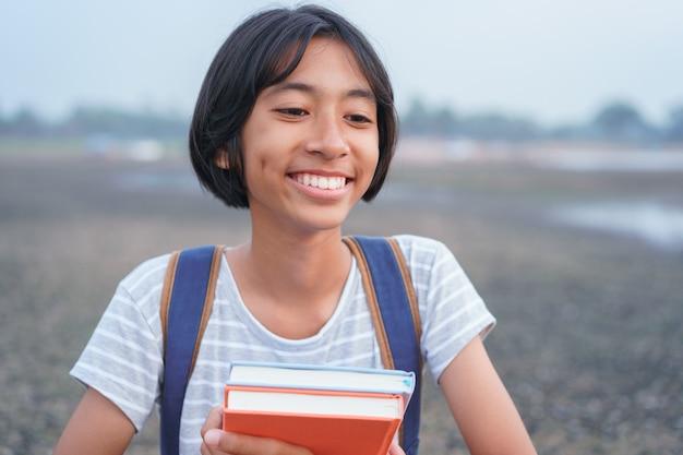 Menina asiática feliz sorrir no rosto e rir em pé em meio à natureza de manhã, criança asiática segura livro e mochila