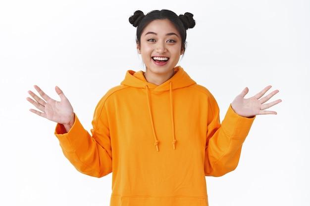 Menina asiática feliz surpresa levanta as mãos pronta para pegar alguma coisa, fica surpresa ao ouvir uma notícia incrível, sorrindo de júbilo e triunfando, parada divertida sobre uma parede branca