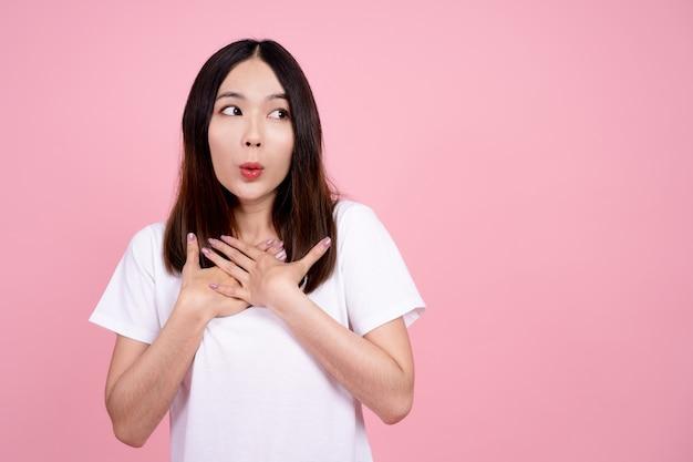 Menina asiática fica surpresa por ela estar animada. estúdio de fundo rosa. Foto Premium