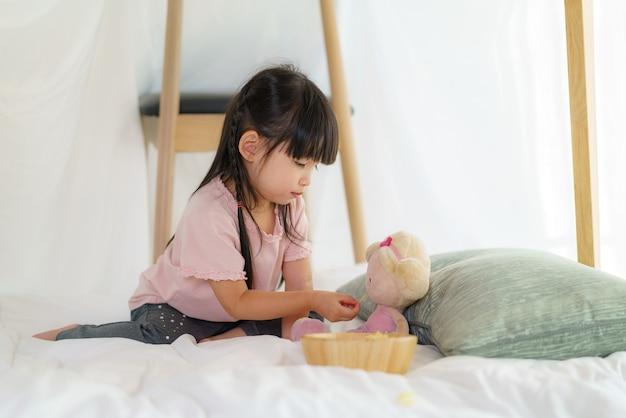 Menina asiática fofa brincando de boneca e comendo lanche enquanto está sentada em um forte de cobertor na sala de estar