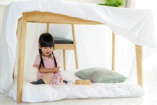 Menina asiática fofa brincando de boneca enquanto está sentada em um forte de cobertores na sala de estar em casa