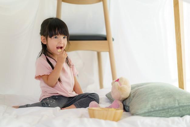 Menina asiática fofa comendo lanche enquanto está sentada em um forte de cobertor na sala de estar em casa