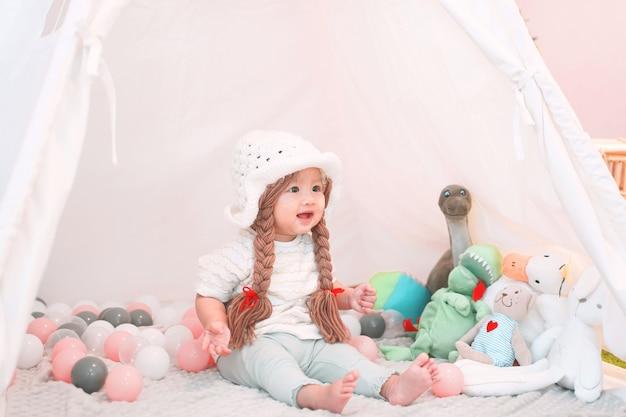 Menina asiática fofa e adorável está brincando com bonecos na tenda teepee.