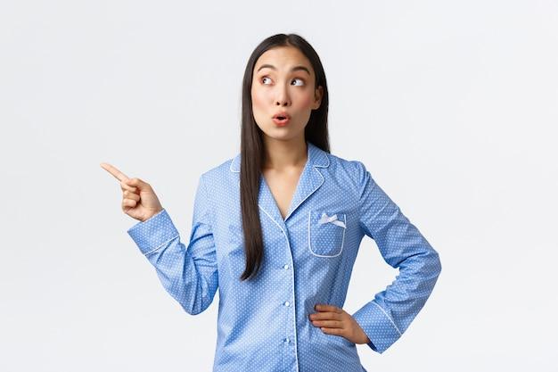 Menina asiática fofa intrigada e animada dizendo uau, apontando e olhando no canto superior esquerdo, vestindo pijama para a festa do pijama, indo dormir e vendo algo curioso, parede branca