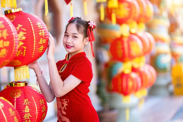 Menina asiática fofa vestindo vermelho tradicional chinês cheongsam com lanternas de papel com o alfabeto chinês bênçãos escritas nela é uma bênção da fortuna decoração para o ano novo chinês