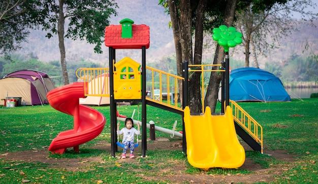 Menina asiática gosta de brincar em um parque infantil