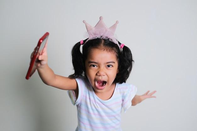 Menina asiática gritando enquanto corre para a frente com a mão segurando um telefone celular