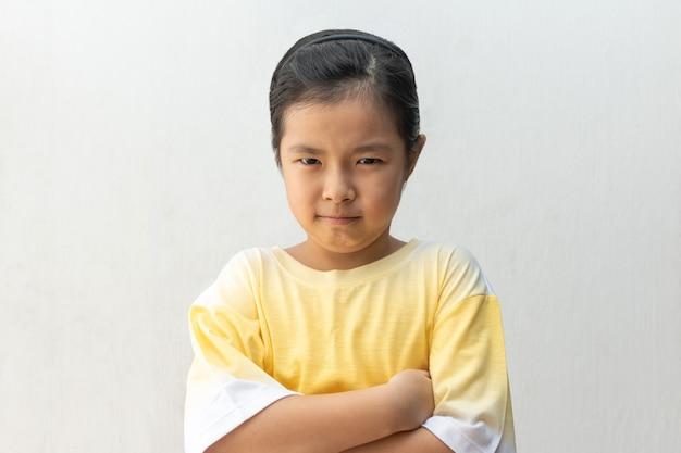 Menina asiática infeliz ou ofendida, isolada no branco.
