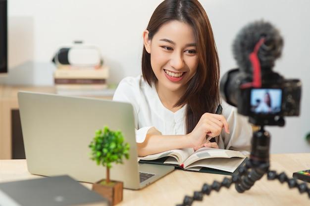 Menina asiática influenciadora feliz falando na frente da câmera para o vlog em casa. jovem mulher de negócios japonesa trabalhando como blogueira gravando vídeo tutorial em streaming ao vivo para internet