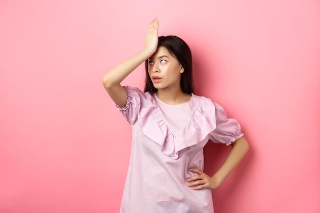 Menina asiática irritada revira os olhos e a palma da mão, sentindo-se cansada e irritada com uma conversa estúpida, de pé contra um fundo rosa.