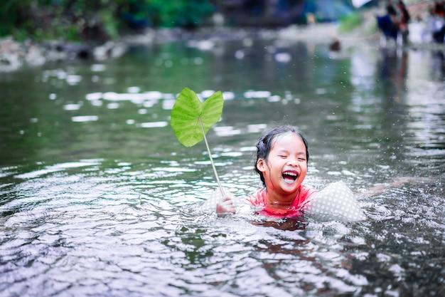 Menina asiática jogando água com folha de lótus em um riacho natural