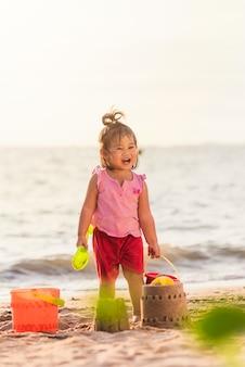 Menina asiática jogando areia com ferramentas de areia de brinquedo em uma praia tropical