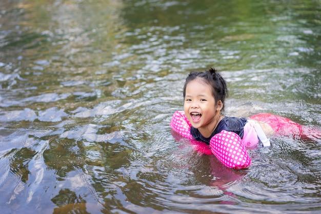 Menina asiática jogando no rio