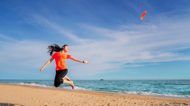 Menina asiática jogar disco voador na praia