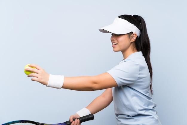 Menina asiática jovem adolescente jogando tênis