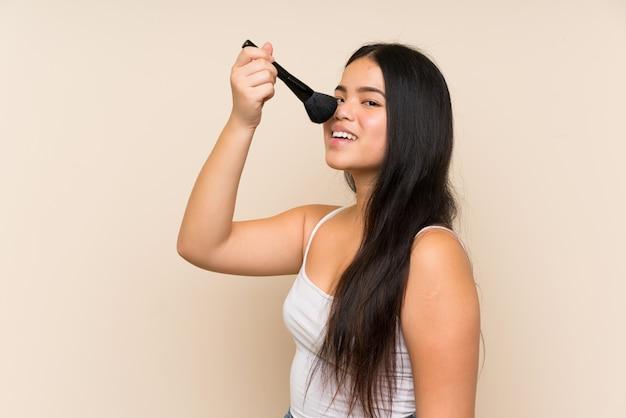 Menina asiática jovem adolescente segurando o pincel de maquiagem