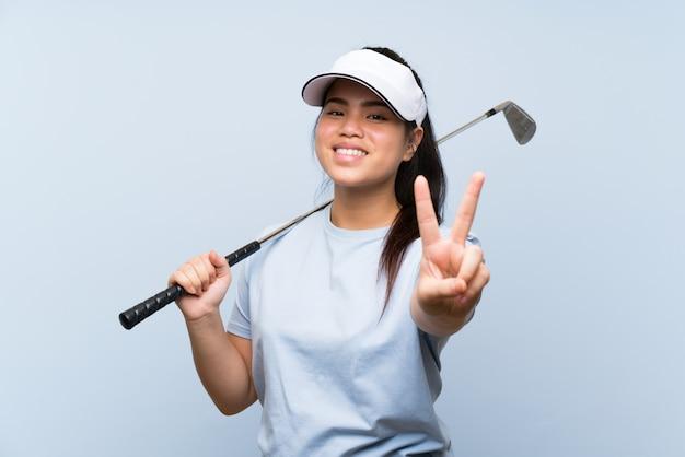Menina asiática jovem jogador de golfe sobre parede azul isolada, sorrindo e mostrando sinal de vitória