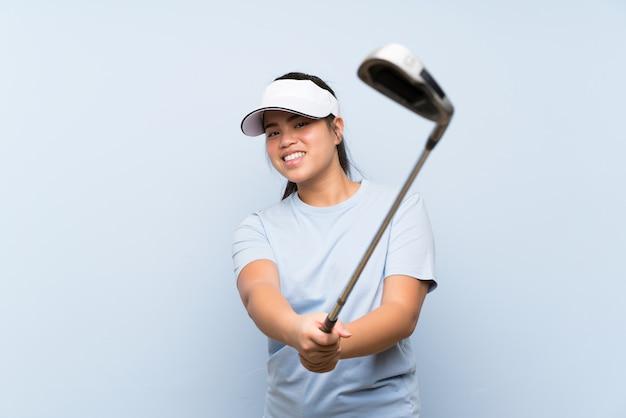 Menina asiática jovem jogador de golfe sobre parede azul isolada