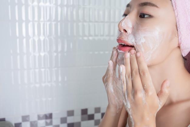 Menina asiática lava o rosto.