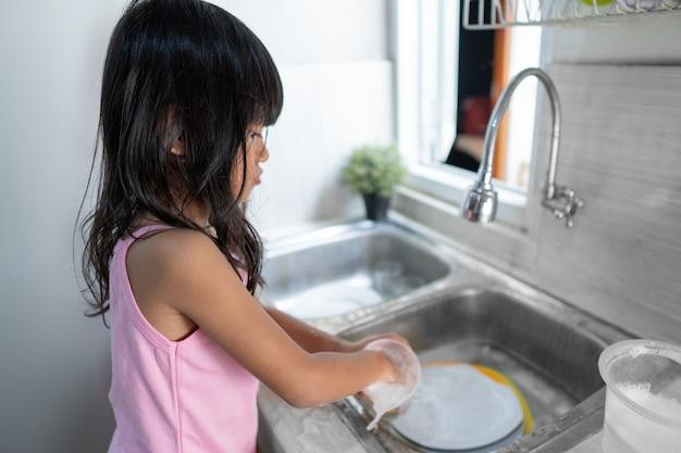 Menina asiática lavando pratos na cozinha