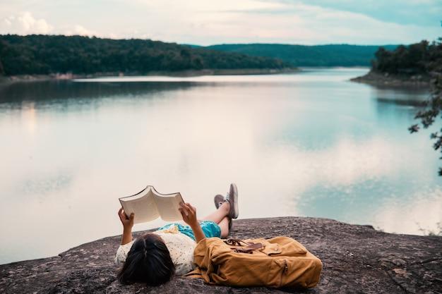 Menina asiática, lendo um livro à beira do lago