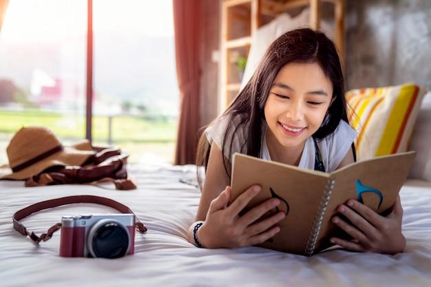 Menina asiática ler um caderno de viagem na cama em pedra de afiar